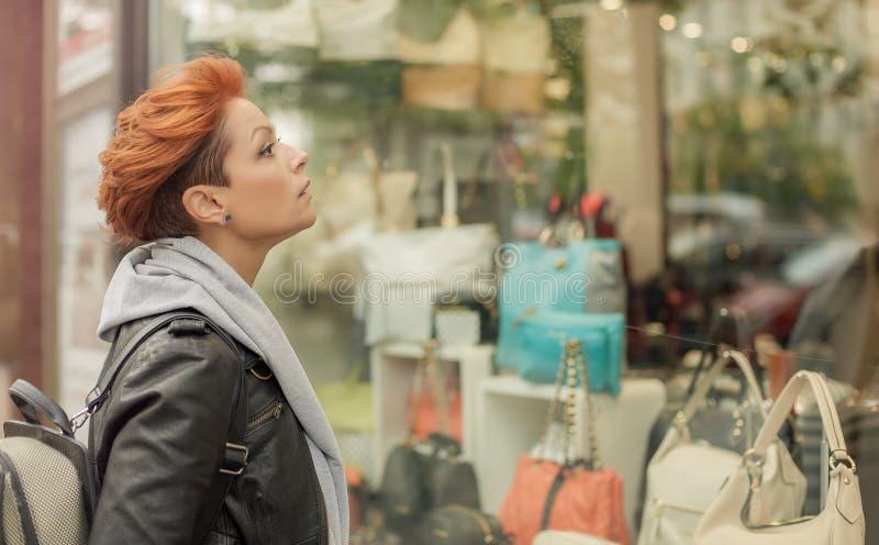 Kvinna som ser i ett shoppafönster med handväskor royaltyfri foto
