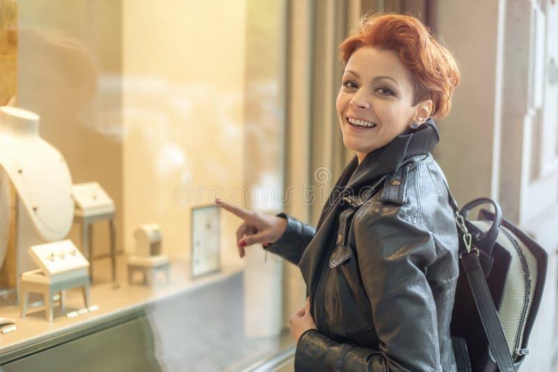 Kvinna som ser i ett shoppafönster med smycken fotografering för bildbyråer