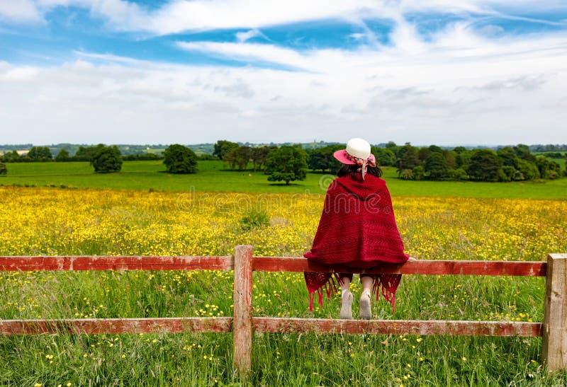 Kvinna som ser in i fält, medan sitta på staketet arkivbild