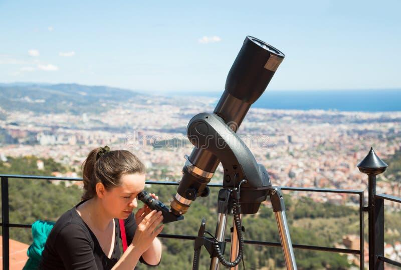 Kvinna som ser i teleskop fotografering för bildbyråer