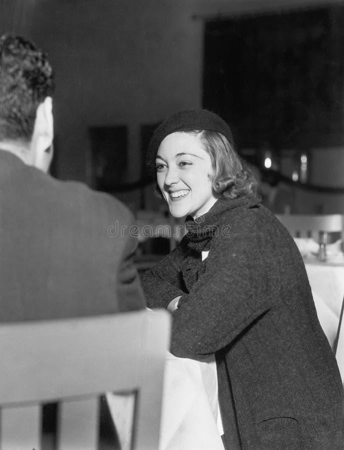 Kvinna som ser jätteglad på en man i en restaurang (alla visade personer inte är längre uppehälle, och inget gods finns Leverantö arkivbild