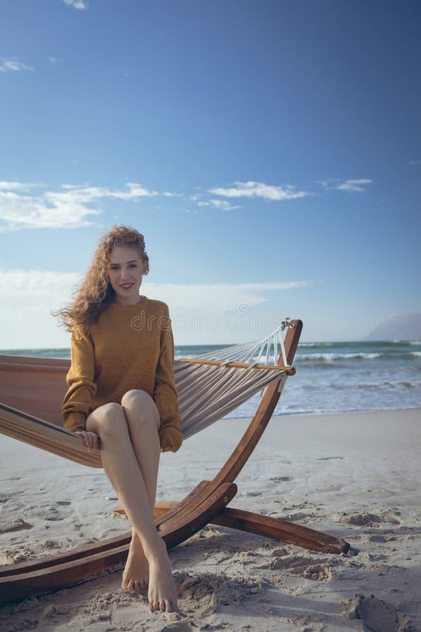 Kvinna som ser kameran som sitter på hängmattan på stranden arkivbilder
