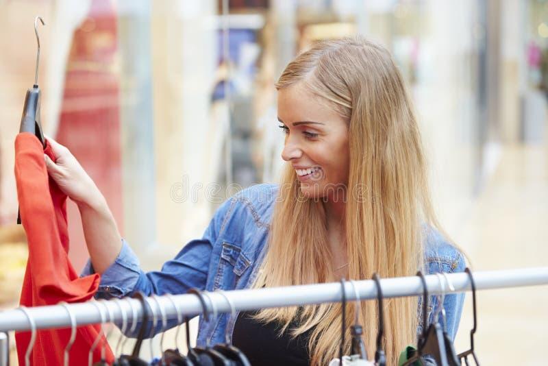 Kvinna som ser kläder på stången i shoppinggalleria royaltyfri fotografi
