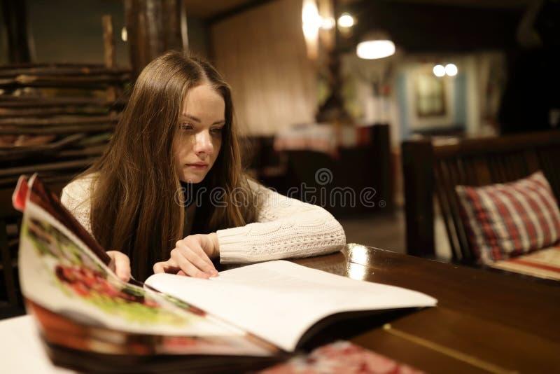 Kvinna som ser menyboken arkivfoton