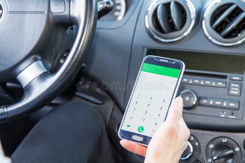Kvinna som ser mobiltelefonen i bil arkivbilder