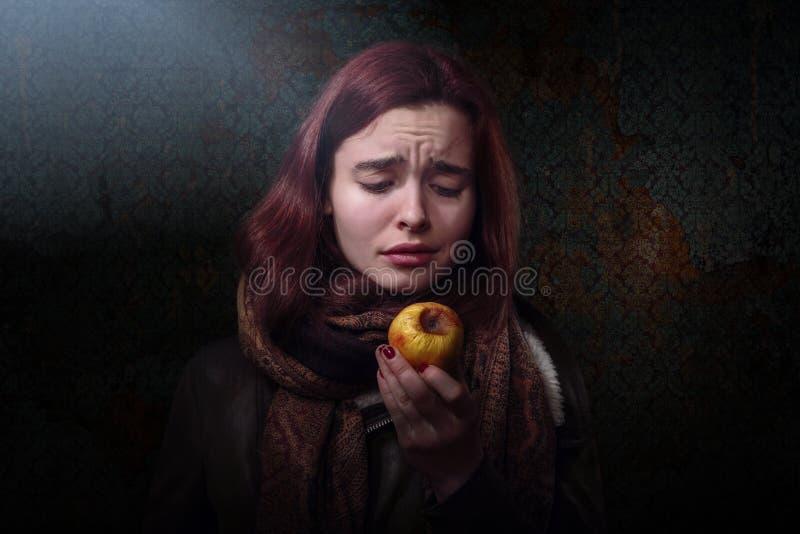 Kvinna som ser på ett ruttet äpple royaltyfria foton