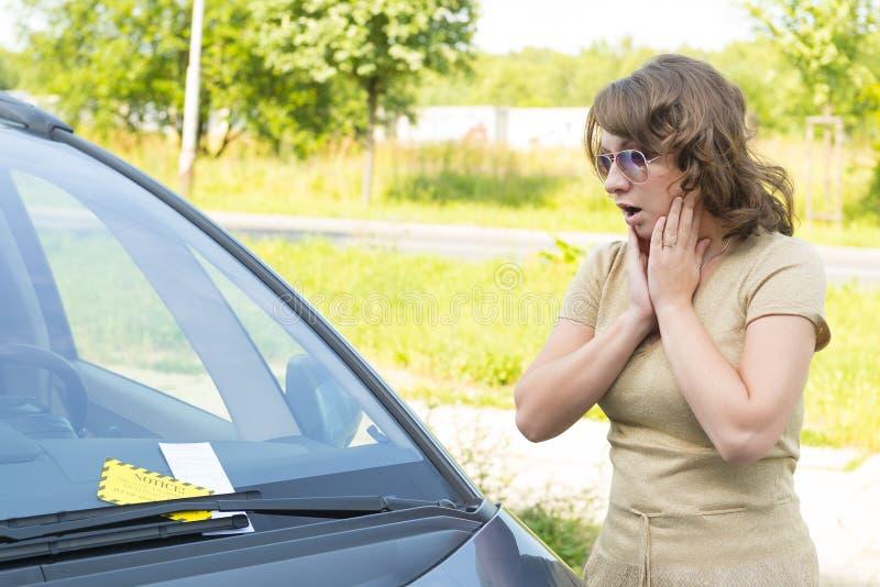 Kvinna som ser på parkeringsbiljett royaltyfria bilder