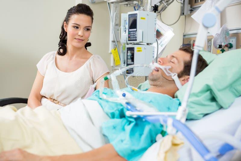 Kvinna som ser patienten som vilar på säng arkivfoton