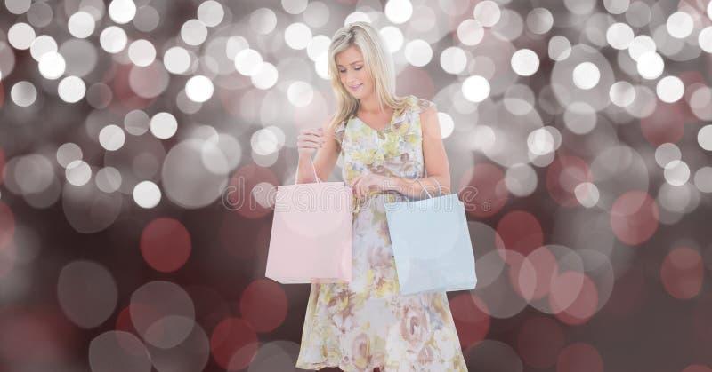 Kvinna som ser shoppingpåsen över suddighetsbakgrund royaltyfria bilder
