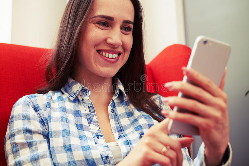Kvinna som ser smartphonen och att le arkivfoton