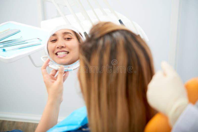 Kvinna som ser spegeln, når att ha gjort vit tänder royaltyfri bild