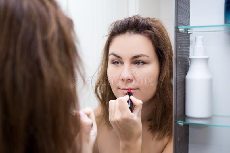 Kvinna som ser spegeln och applicerar läppstift i badrum royaltyfri fotografi