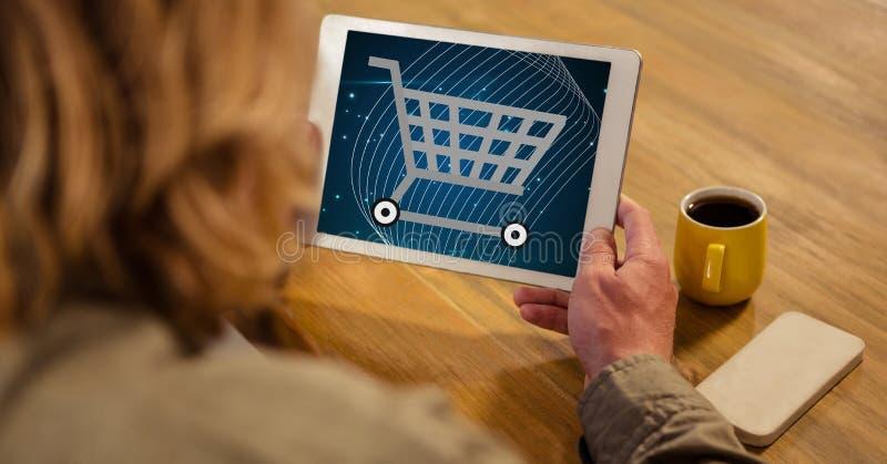 Kvinna som ser symbolen för shoppingvagn på minnestavlaPC royaltyfri illustrationer