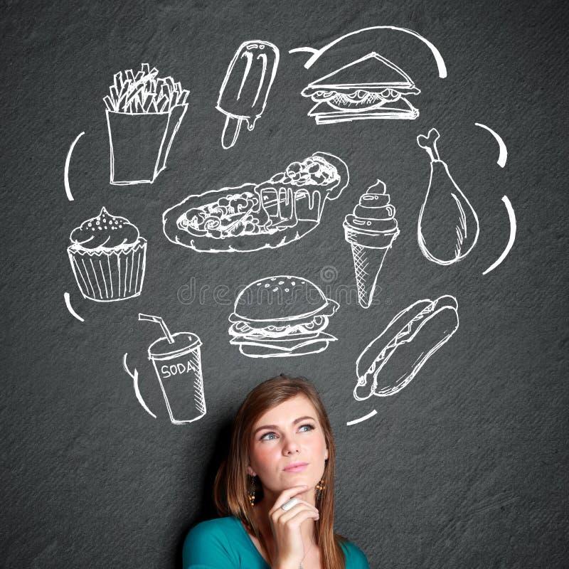 Kvinna som ser tänka upp vad för att äta royaltyfri bild
