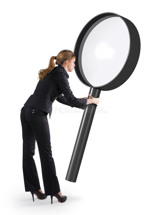 Kvinna som ser till och med ett förstoringsglas arkivbild