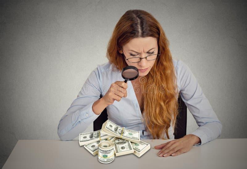Kvinna som ser till och med förstoringsglaset på bunt av dollarsedlar royaltyfri fotografi