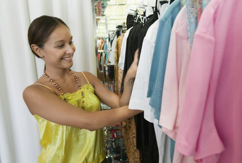 Kvinna som ser till och med klädkuggen i lager arkivbilder