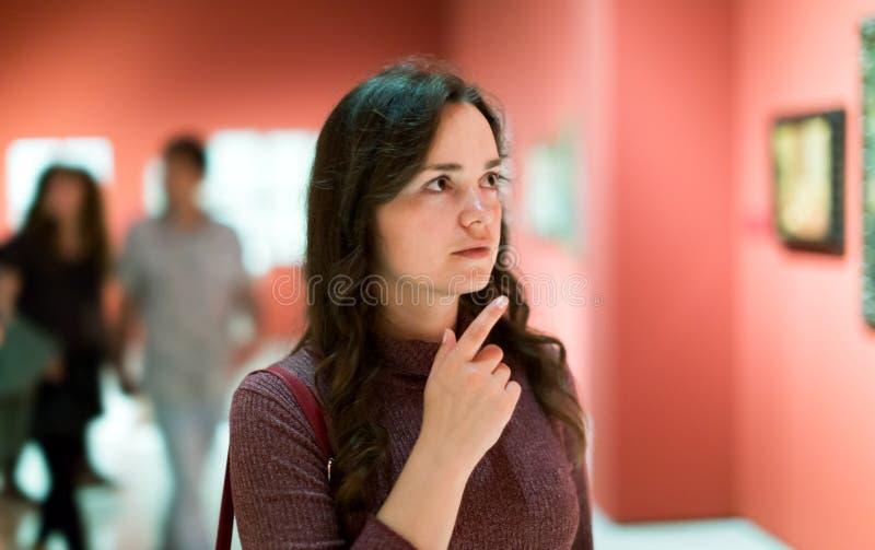 Kvinna som ser uppmärksamt målningar i konstmusem arkivbild
