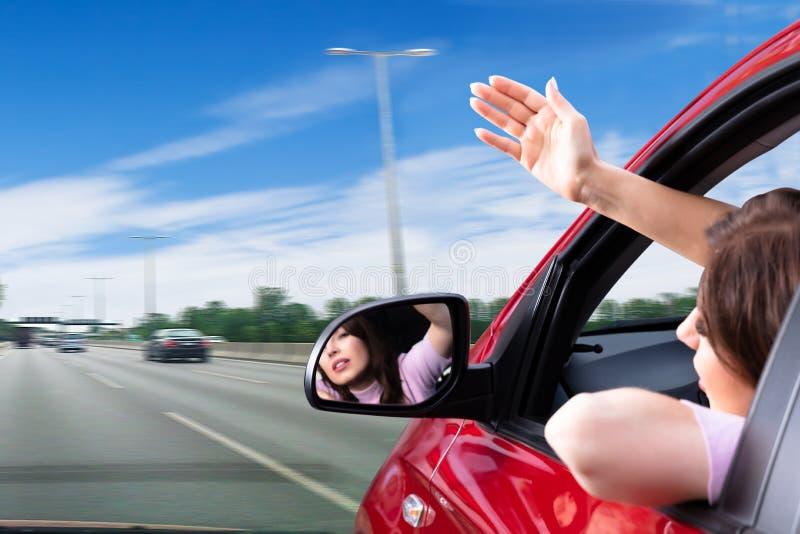 Kvinna som ser ut ur bilf?nster royaltyfri foto