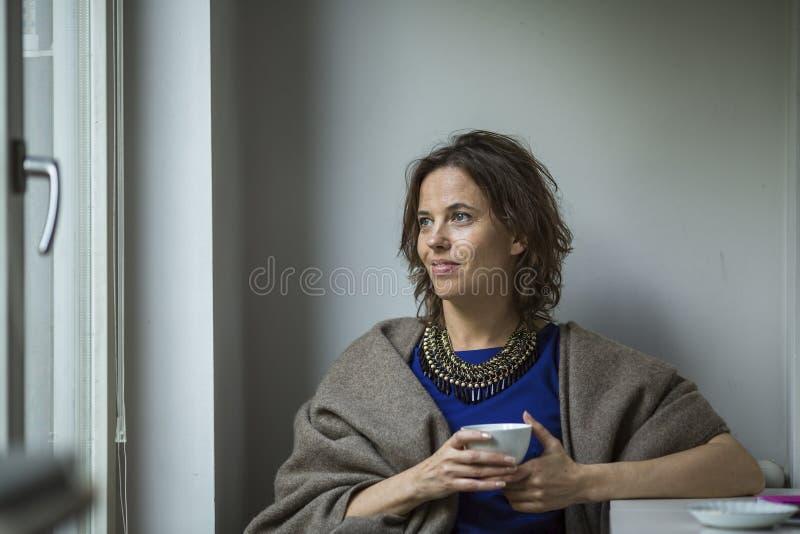 Kvinna som sitter hänsynsfullt med en kopp te arkivbilder