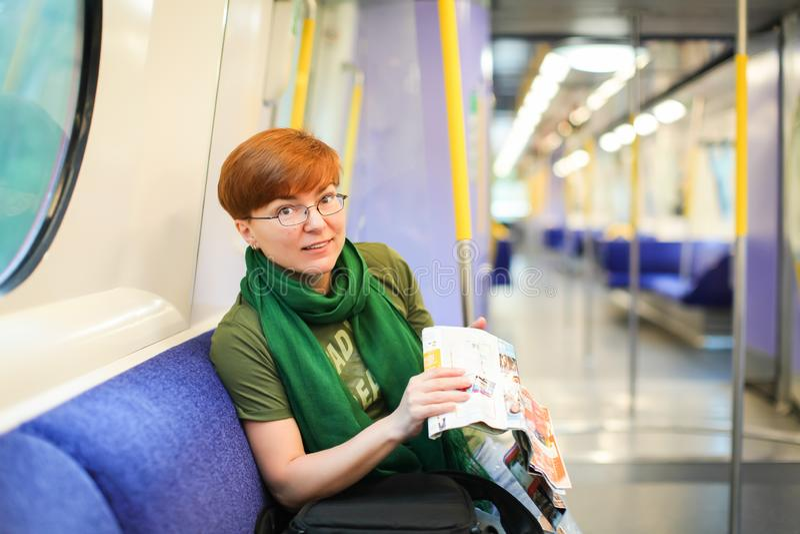 Kvinna som sitter i drev och studerar ruttöversikten Caucasian rödhårig manturist i exponeringsglas i vagn av tunnelbanan handels royaltyfri foto