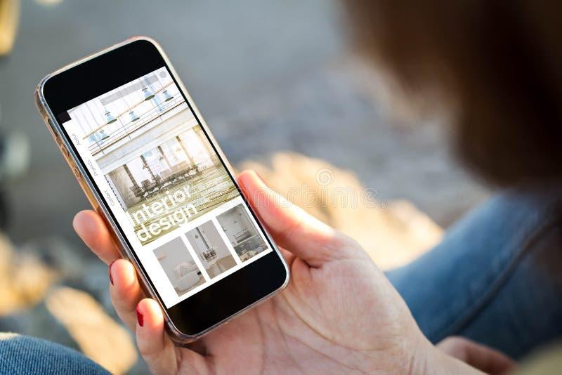 kvinna som sitter i gatan som rymmer hennes smartphone som visar websiten för inredesign arkivbilder