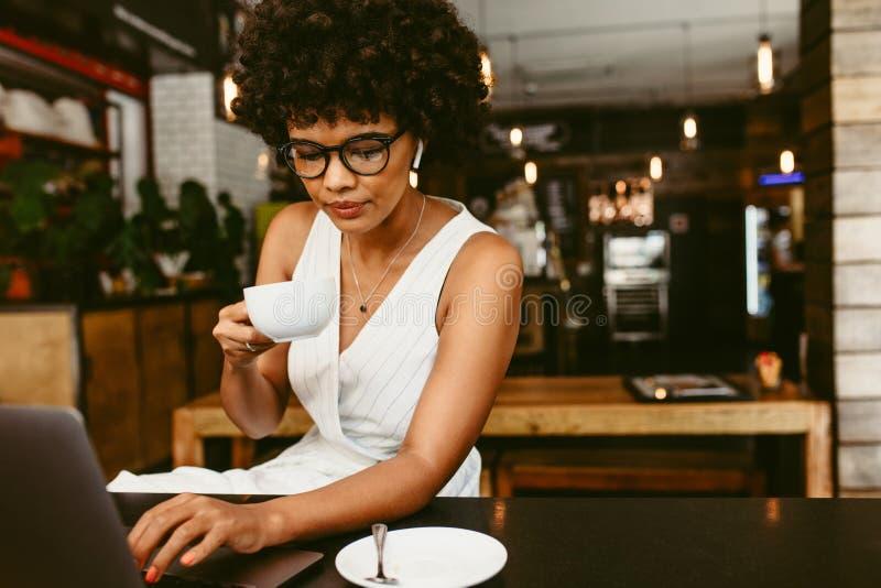 Kvinna som sitter i kafé med en bärbar dator royaltyfri fotografi