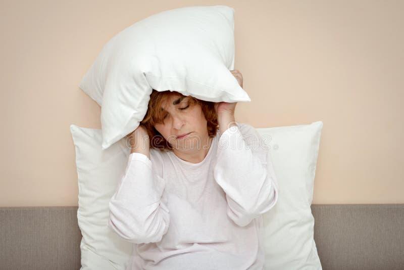 Kvinna som sitter i säng med kudden över hennes huvud royaltyfri fotografi