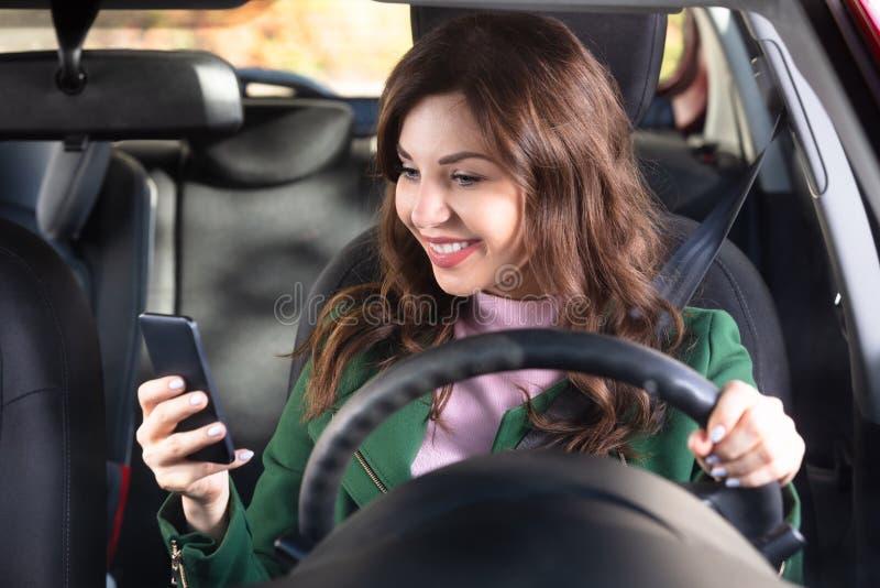 Kvinna som sitter inom bilen genom att anv?nda mobiltelefonen royaltyfria foton