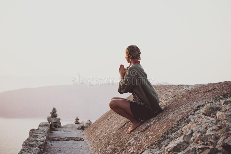 Kvinna som sitter och mediterar på stenar i Monolithos, Rhodes, Grekland arkivbilder