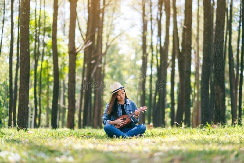 Kvinna som sitter och spelar ukulelet i det fria fotografering för bildbyråer
