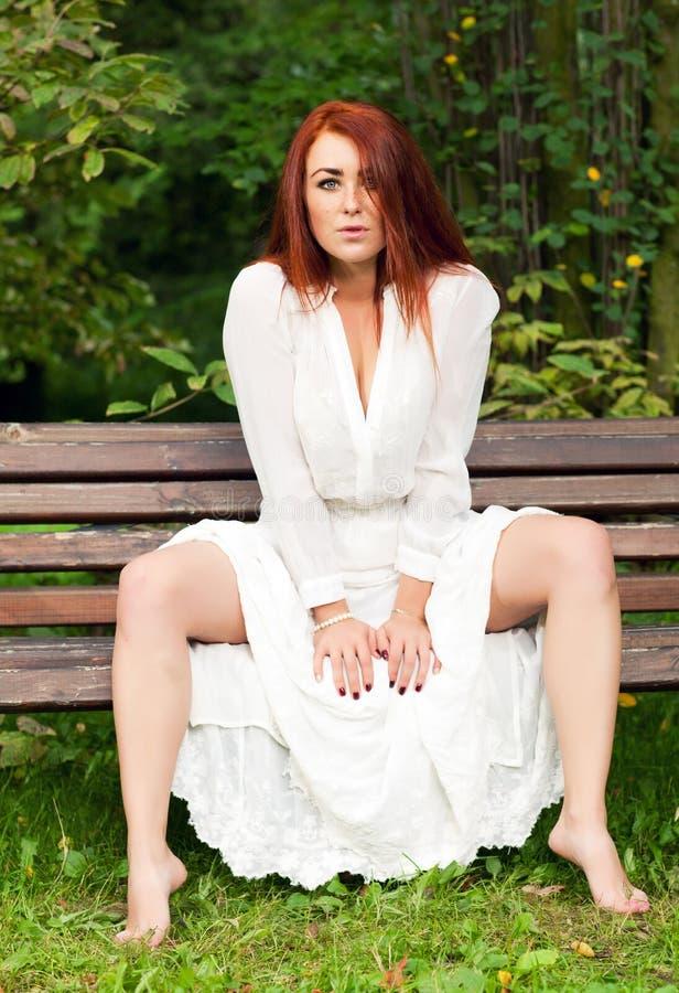 Download Kvinna som sitter på bänk fotografering för bildbyråer. Bild av fokus - 76702393