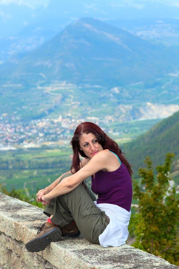 Kvinna som sitter på en avsats. royaltyfria bilder