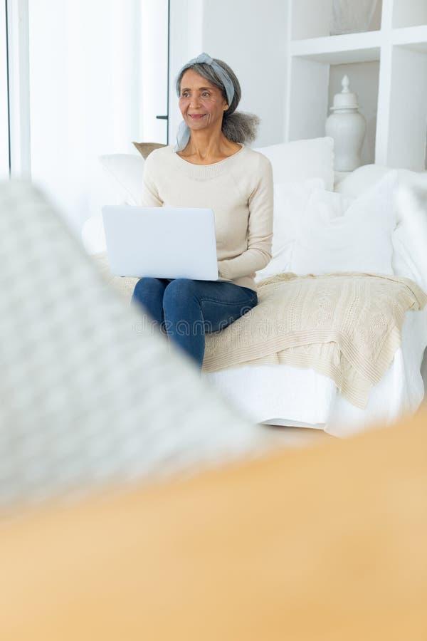 Kvinna som sitter på en soffa i ett vitt rum, medan genom att använda en vit bärbar dator fotografering för bildbyråer