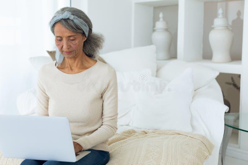 Kvinna som sitter på en soffa i ett vitt rum, medan genom att använda en vit bärbar dator royaltyfri fotografi