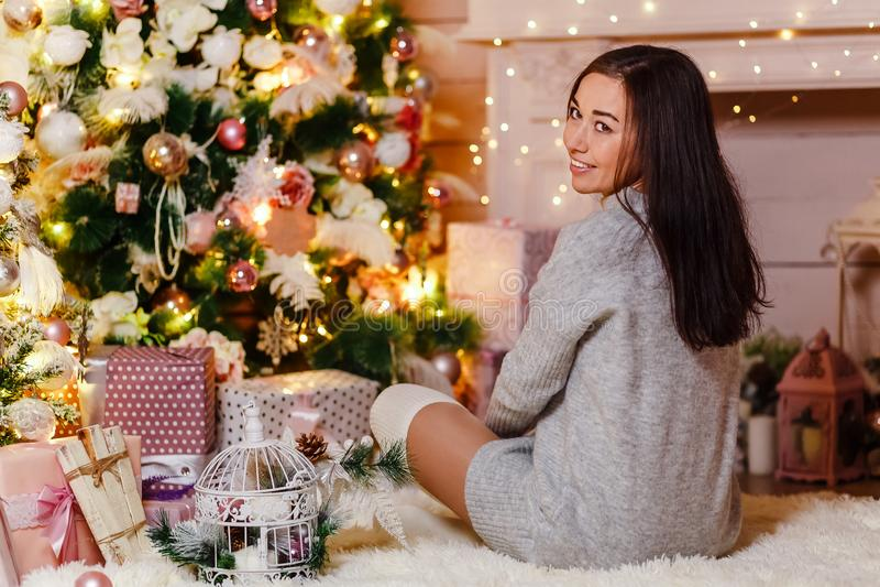 Kvinna som sitter på golvet nära en julgran arkivfoton