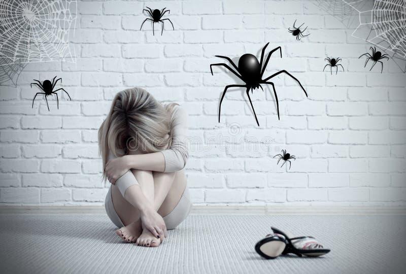 Kvinna som sitter på golvet och ser på imaginär spindel royaltyfri foto