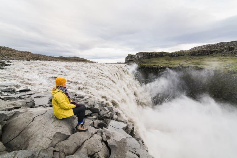 Kvinna som sitter på klippkanten bredvid den Dettifoss vattenfallet i den Vatnayokull nationalparken, Island fotografering för bildbyråer