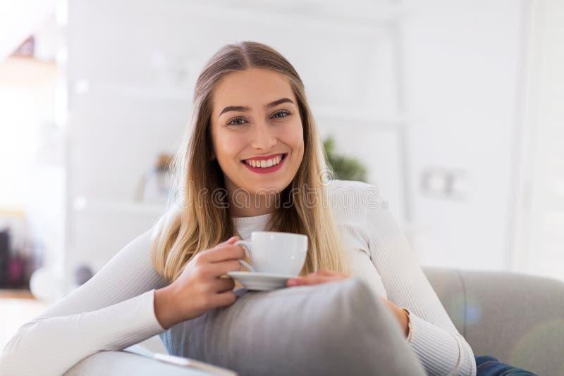 Kvinna som sitter på soffan med koppen kaffe royaltyfri bild