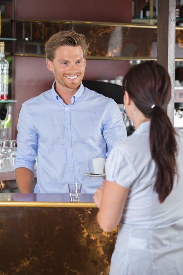 Kvinna som sitter på stången som talar med bartendern arkivfoto