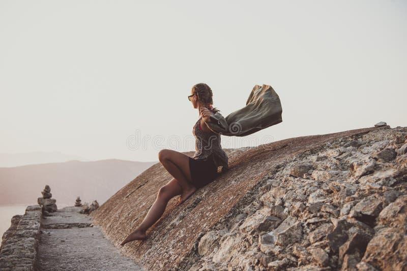 Kvinna som sitter på stenar i den Monolithos slotten i Rhodes, Grekland royaltyfri foto