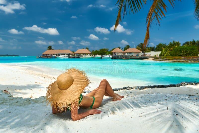 Kvinna som sitter på stranden under palmträdet arkivfoton