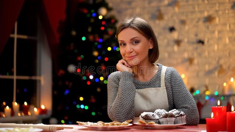 Kvinna som sitter på tabellen med chokladmuffin och in camera ser, Xmas-recept royaltyfri fotografi