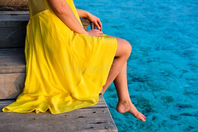 Kvinna som sitter p? strandbryggan arkivfoton