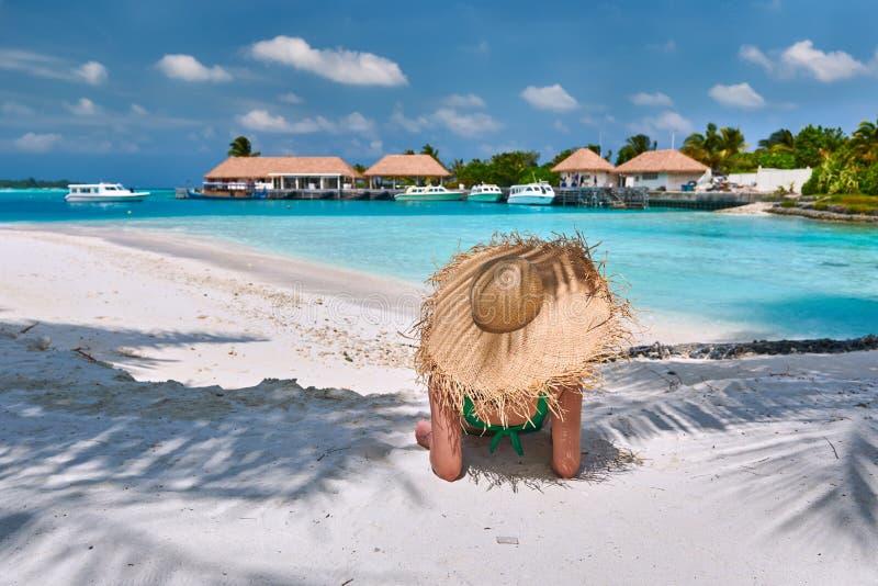 Kvinna som sitter p? stranden under palmtr?det royaltyfri bild