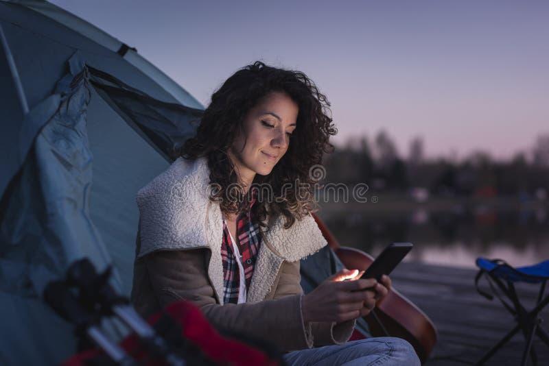 Kvinna som sitter vid tältet royaltyfria foton