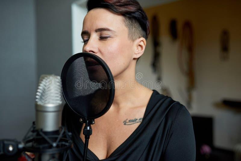 Kvinna som sjunger i solid studio arkivfoto