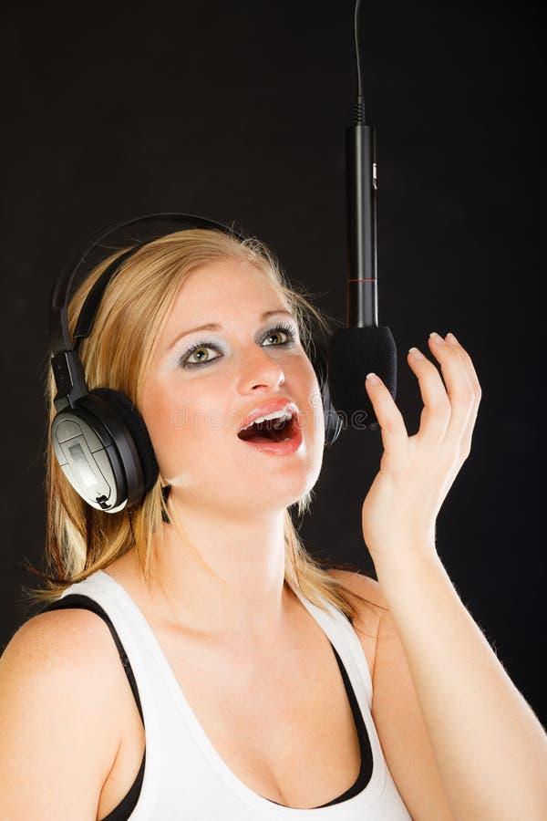 Kvinna som sjunger till bärande hörlurar för mikrofon i studio arkivbilder