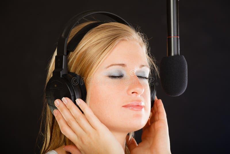 Kvinna som sjunger till bärande hörlurar för mikrofon i studio fotografering för bildbyråer
