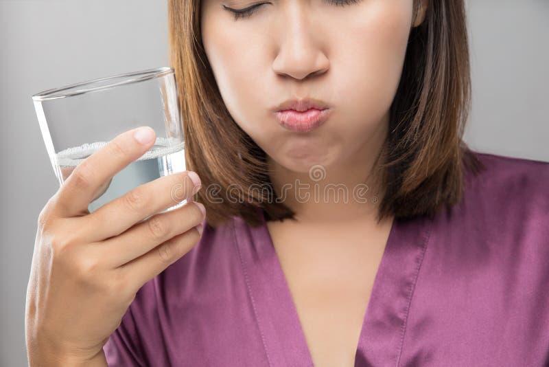 Kvinna som sköljer och gurglar, medan genom att använda munvatten från ett exponeringsglas royaltyfri foto